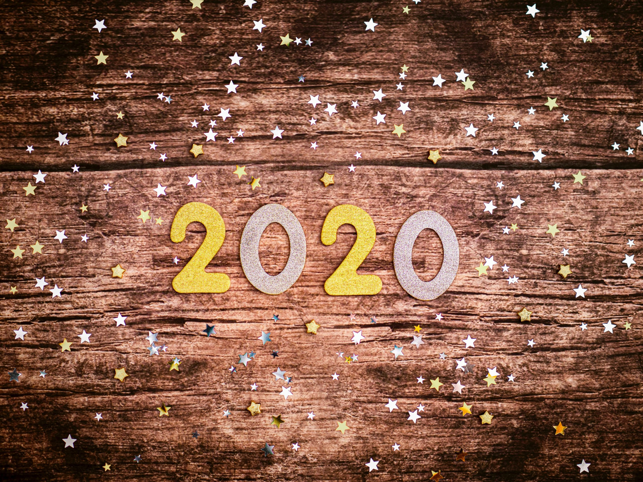 The numbers 2020 in glittery numbers surrounded by gold and silver stars.